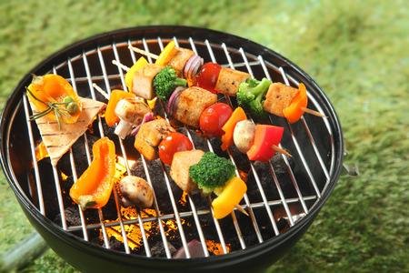 pinchos morunos: Kebabs tofu con verduras frescas de colores incluyendo cebolla, pimiento, queso de soja, champi�ones, br�coli y tomate roscados en los pinchos parrilla sobre el fuego en una barbacoa Foto de archivo