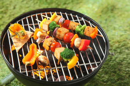 grill: Tofu kebabs with colorful fresh vegetables including onion, sweet pepper, tofu,mushroom, broccoli and tomato threaded on skewers grilling over the fire on a BBQ