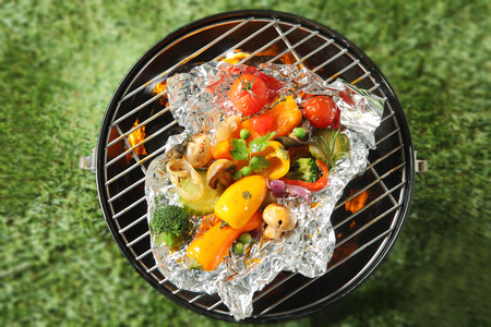 vegetable tin: Vegan or vegetarian summer barbecue with assorted diced fresh vegetables including peas, bell pepper, onion, broccoli, mushrooms, tomato cooking in tin foil over the fire, overhead view on green grass