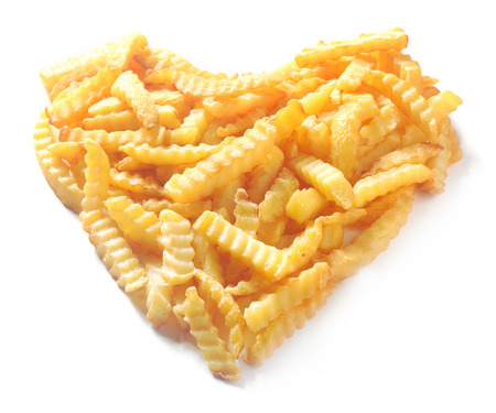 Heart shape formed from crinkle cut potato chips isolated on white in a conceptual image of love or romance Banco de Imagens