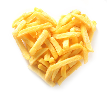 Overhead Still Life of Straight Cut French Fries in Shape of Heart on White Background