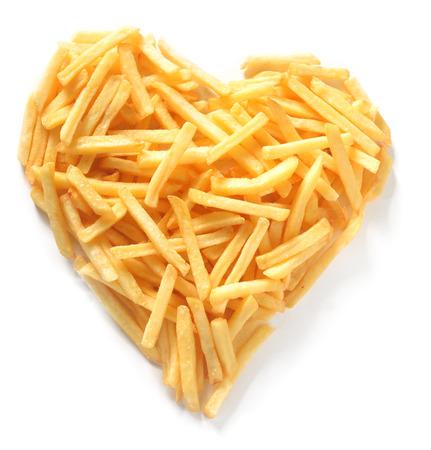 Overhead Bodegón de papas fritas de corte delgado y recto franceses en forma de corazón asimétrica en el fondo blanco
