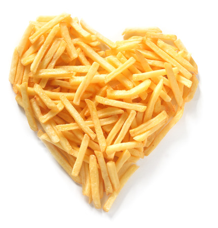 fast: Overhead Still Life of Thin Straight Cut French Fries in Shape of Assymmetrical Heart on White Background