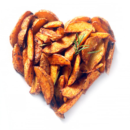 wedges: Delicious arrangement of spicy seasoned potato or sweet potato wedges arranged in a heart shape and seasoned with rosemary symbolic of love and romance, overhead on white