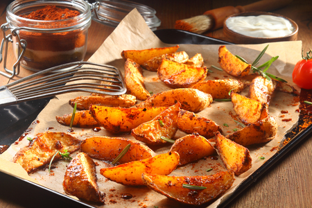 ovenbaked: Close up Appetizing Spicy Potato Wedges on Black Tray with Paper, Served on Wooden Table