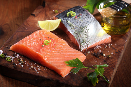 Close up Uncooked Fresh Salmon Fish Slices on Wooden Cutting Board with Herbs and Spices photo