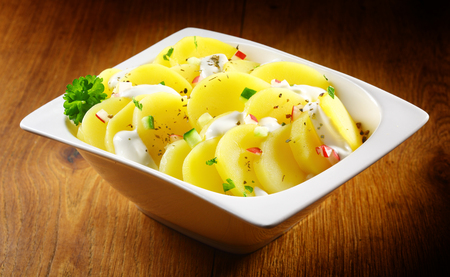 side salad: Close up Gourmet Boiled german Potato salad with Herbs and Spices on White Bowl Placed on Wooden Table.