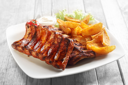 Close up Gourmet Main Dish with Grilled Pork Rib and Fried Potatoes on White Plate. Served on Wooden Table.