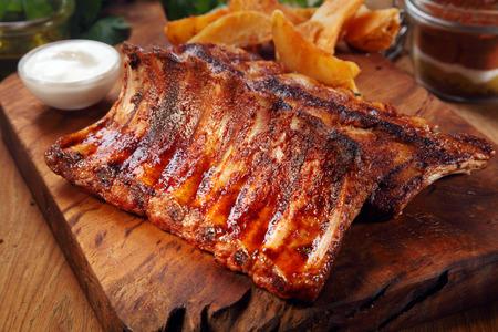 Close-up de dar água na boca suculenta carne de porco grelhada costela em cima da tábua de madeira Foto de archivo - 36832998