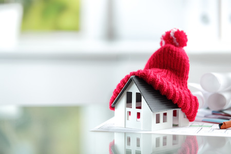 warm clothing: Close up Conceptual of Insulation Symbol House with Red Bonnet in office burreau. Stock Photo
