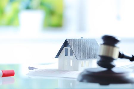 Close up Konzeptionelle Weiß Little House on Top of Documents auf dem Tisch neben Hölzerner Hammer auf einer Auktion verkaufen