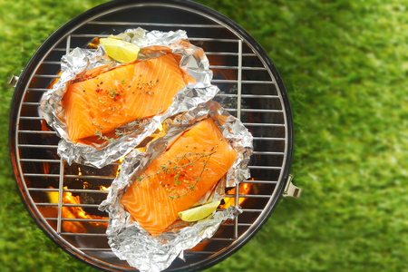 coals: Gourmet salmon steaks grilling on a barbecue in tin foil wrappers garnished with leomon wedges, overhead view