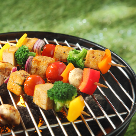 barbecued: Tofu skewers with colorful vegetables including broccoli, sweet pepper,smoked tofu, tomatoes , onions and mushrooms, grilling on a barbecue