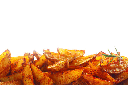 fried foods: Border of tasty spicy fried potato wedges or jacket potatoes, sweet potatoes or yams over white with copyspace for your menu, text or advertising