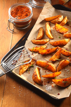 wedges: Close up Tasty Fried Potato Slices on Tray with Slotted Ladle, Placed on Wooden Table with Spicy Powder on the Side. Stock Photo