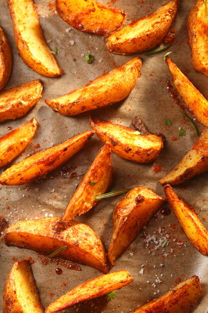 wedges: Close up Freshly Cooked Hot Spicy Potato Wedges on Top of a Brown Paper