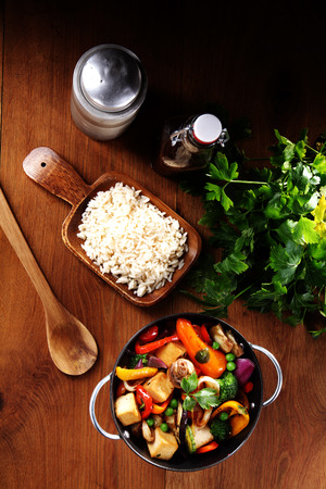 Aerial Shot of Healthy Recipe, with Vegetable and Spices, and Cooked Rice on Wooden Table with Ladle, Herbs and Sauce photo