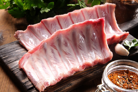 Close up Raw Pork Rib Meat Ingredient on Top of Rustic Wooden Cutting Board Archivio Fotografico