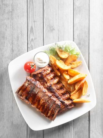 pork rib: Vicino colpo aerea di maiale alla griglia Rib carne, fritti croccanti patate con salsa sul piatto bianco. Immessi sul grigio Tabella di legno.