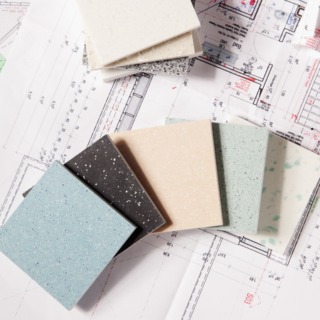 tiler: Close up Different Choices of Tile Texture Designs for Housing on Top of a Printed Blueprint.