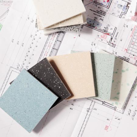 Close up Verschiedene Auswahl von Fliesen Textur Designs für Wohnungswesen oben auf einen Gedruckt Blueprint.