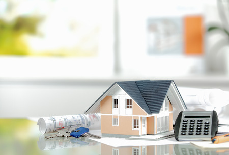 private insurance: Owning Real Property Concept - Close up Miniature Model House on Top of the Table with Key and Calculator Device Stock Photo