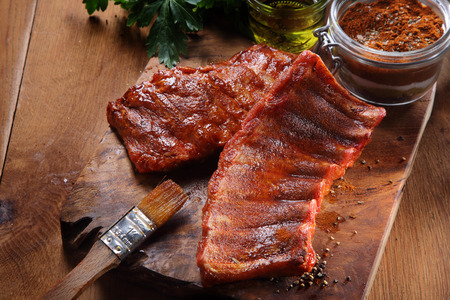 marinate: Close up Juicy Fried Pork Rib Meat on a Wooden Cutting Board with Spicy Powder. Placed on Wooden Table. Stock Photo