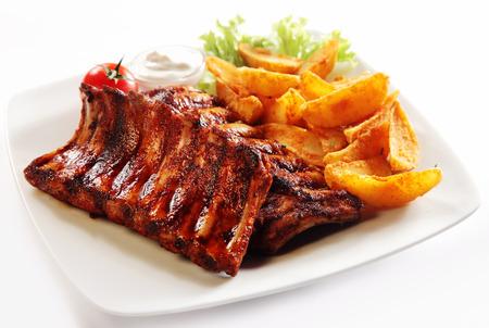흰 배경에 고립 된 소스와 채소, 하얀 접시에 음식 구운 돼지 갈비와 튀긴 감자 웨지를 닫습니다.