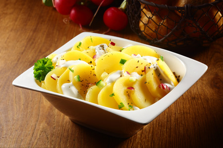 potatoe: Close up Appetizing Flavored Boiled Potato salad with White Cream and Spices on White Bowl. Placed on Wooden Table.