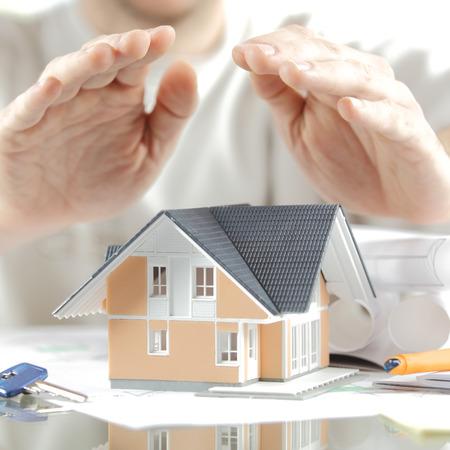 ホーム保険のコンセプト - キー、両側に青写真とテーブルの上の手をカバー ミニチュア モデル家をクローズ アップ。