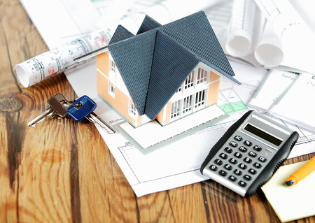 conceptual: Close up View of Conceptual Miniature Model Home on Top of Blueprints, Placed on a Wooden Table, with Keys and Calculator Device.