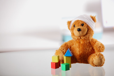 sick teddy bear: Conceptual Bandaged Brown Teddy Bear with Colored Block Shapes on Top of the Table