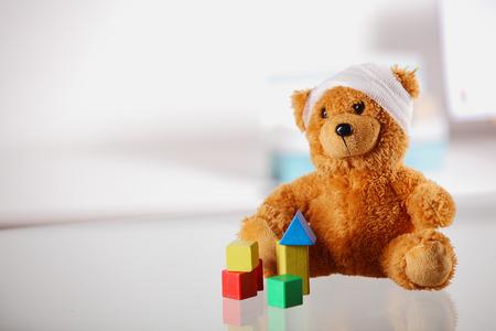 enfant malade: Conceptuel Bandaged Brown Teddy Bear avec bloc de couleur Formes sur Haut de la Table