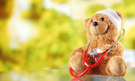 doctor toys: Close up Bandaged Plush Teddy Bear with Stethoscope Device on Top of a Glass Table, Emphasizing Copy Space.