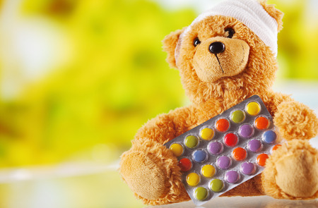 doctors with pills: Conceptual Bandaged Brown Plush Teddy Bear with Foil Packaged Colored Pills