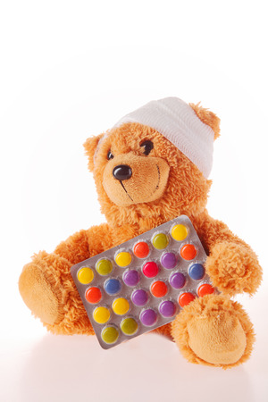pediatrist: Close up Sick Plush Teddy Bear with Bandage on the Head Holding a Foil Packaged Colored Pills, Isolated on White Background. Stock Photo