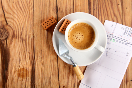 Cup of Brown Coffee on Top of Wooden Table with Small Wooden Bricks, Trowel and Blueprint on the Sides. photo