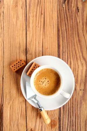 top angle: Aerial Shot of Cup of Brown Coffee on a Plate with Trowel and Small Wooden Bricks on Sides, Placed on Top of a Wooden Table, Emphasizing Copy Space.