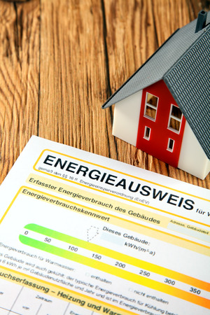 economise: Energy report for a house purchase or sale which rates the efficiency of usage and consumption with a German title alongside a model house on a wooden table Stock Photo