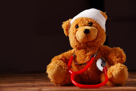 paediatrician: Conceptual Bandaged Plush Teddy Bear with Red Stethoscope Device o Top of the Wooden Table with Dark Brown Background.