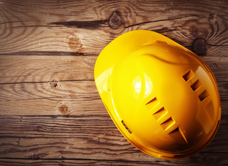 safety gear: Close up Yellow Safety Engineer Helmet Gear on Top of Brown Wooden Table
