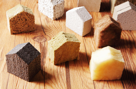 Close up Various Scattered Blocks of insulation Model Hous in Different Standing on Top of the Wooden Table photo
