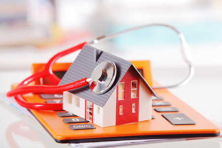 reviewer: Conceptual Simple Model House with Stethoscope on Top of an Orange Calculator Device Placed on White Table.