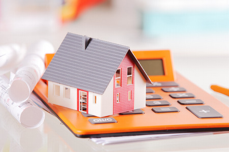 Conceptual Miniature Model Home on Top of an Orange Calculator Device Placed on White Table with Blueprint.
