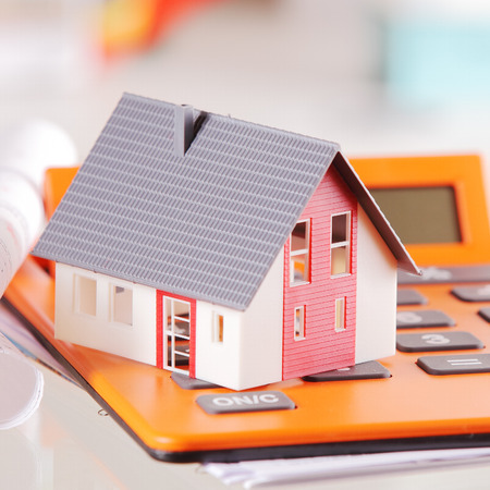 Close up Miniature Model House on Top of an Orange Calculator Device on a White Table. photo