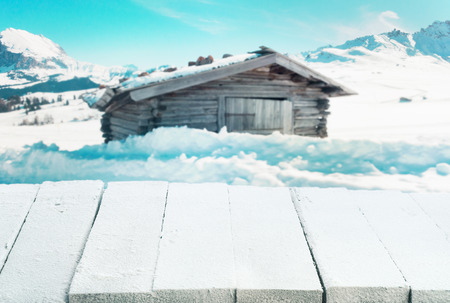 log cabin in snow: Empty rustic wooden snow covered table in the foreground of a winter landscape with a log cabin in snowy mountain scenery suitable for product placement