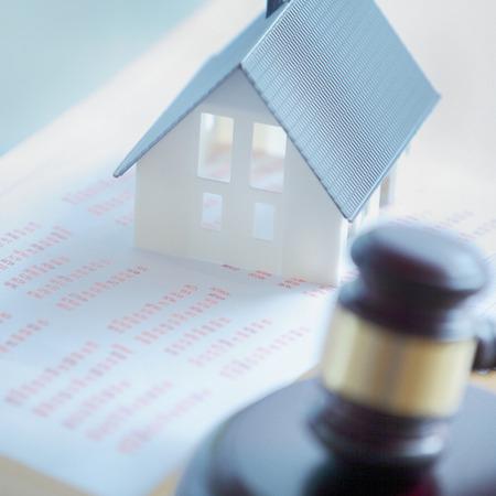 オークション販売でぼやけて裁判所小槌と印刷レポートの上に単純なミニチュアの家を閉じる 写真素材