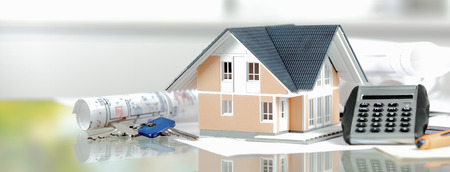 Onroerend goed concept - Miniatuur Model huis op de top van een glazen tafel met Rekenmachine, Toetsen en Blueprint. Stockfoto