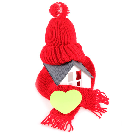 emphasizing: Close up Conceptual Red Wool Scarf Hat with Yellow Green Heart Shape, Emphasizing Copy Space, on Miniature Home. Isolated on White Background.