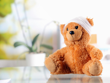 Close up Conceptual Brown Teddy Bear with Bandage on the Head on Top of the Glossy Table